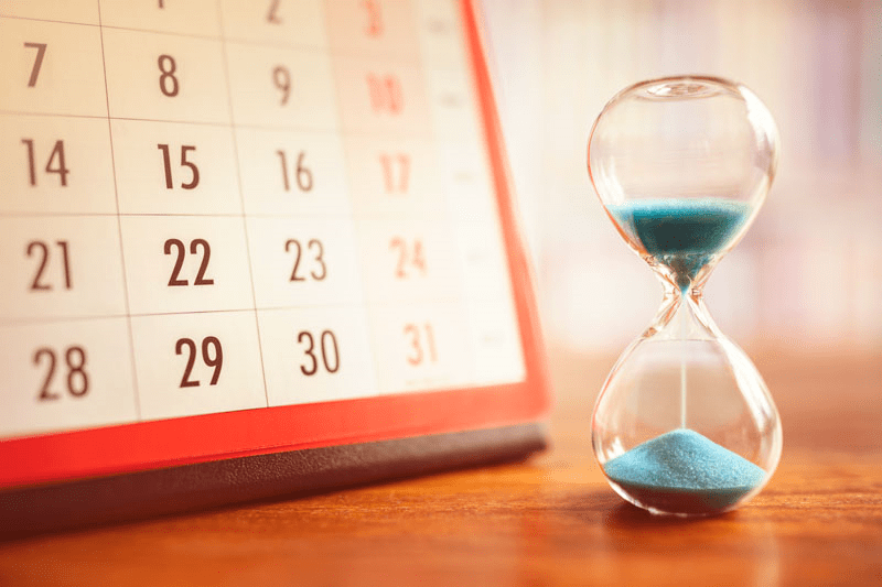 An hour glass with teal sand sits next to a white calendar with black and red numbers.