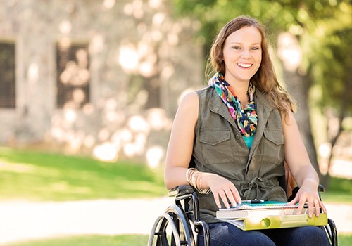 A woman in a wheelchair is outside smiling.