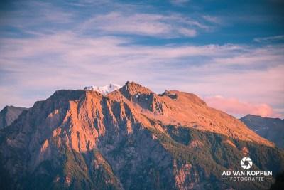 Landschapsfoto van de bergen tijdens een zonsondergang in Wallis Zwitserland. Mooie blauwe lucht met kleine witte wolkjes boven de bergen.