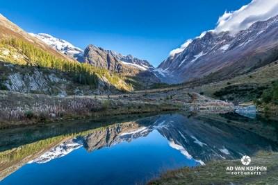 Landschapsfoto van de Grundsee met hierin de weerspiegeling van de bergen in het Lötschental. Mooie blauwe lucht met kleine witte wolkjes boven de bergen.