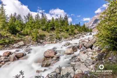 Landschapsfoto van een waterval in het riviertje De Lonza in het Lötschental, Wallis, Zwitserland. Frisse kleuren onder en mooie blauwe lucht met een paar witte stapelwolkjes.