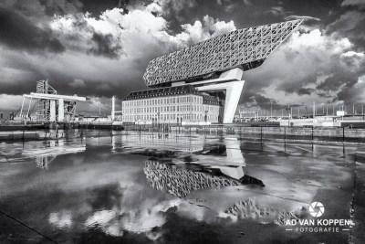 Infraroodfoto in zwart wit van het Havengebouw in Antwerpen met weerspiegeling in de regenplassen.
