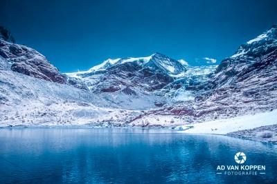 Infraroodfoto van de Turtmannsee. Blauw meer, blauwe lucht en bergen in Wallis Zwitserland.