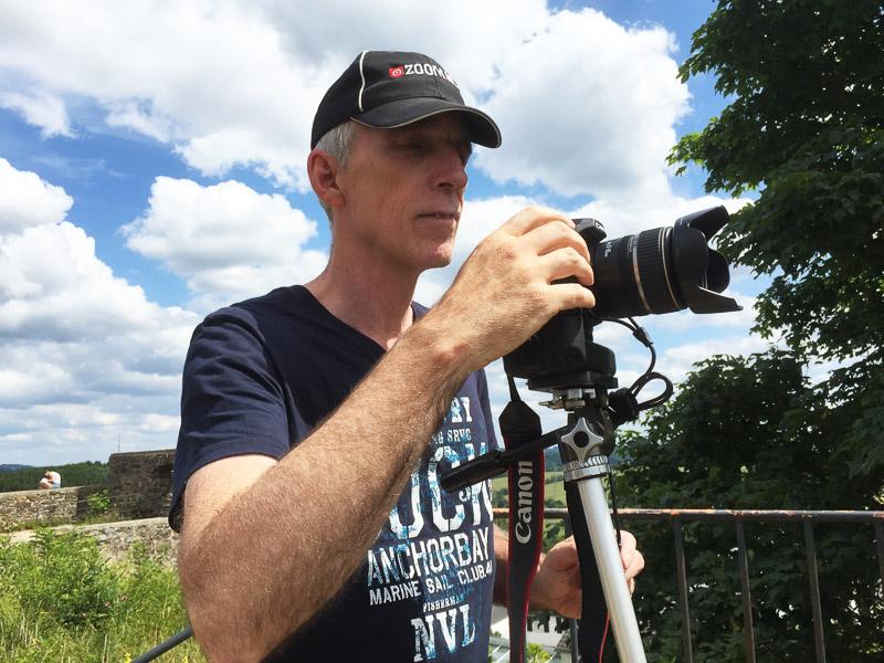 Actiefoto van fotograaf Ad van Koppen aan het werk in de buitenlucht.