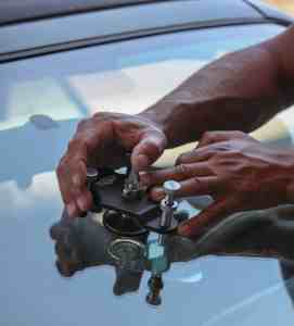 David's hands doing a Chip Repair on a Windshield