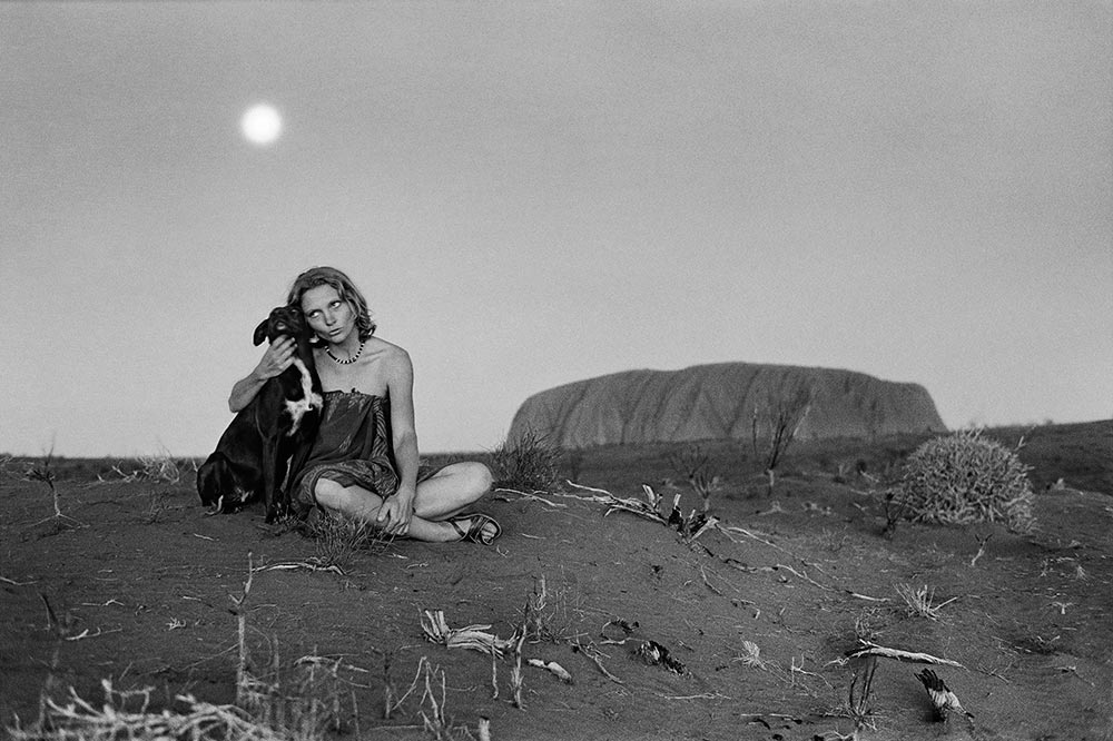 Robyn Davidson and her dog, Diggity, at Uluru, the world's largest rock. Photography by Rick Smolan/Against All Odds Production