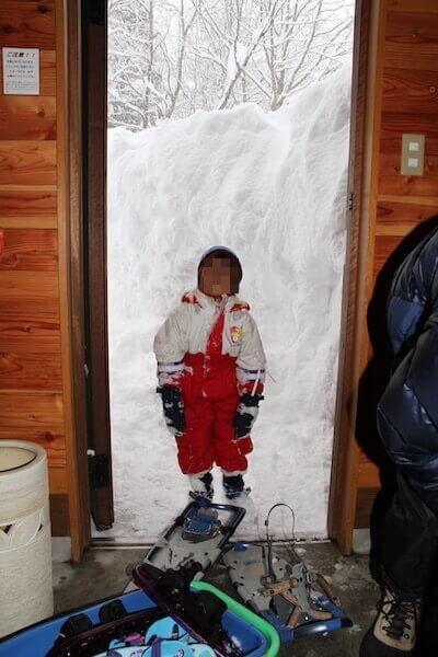 雪で埋まるコテージの玄関
