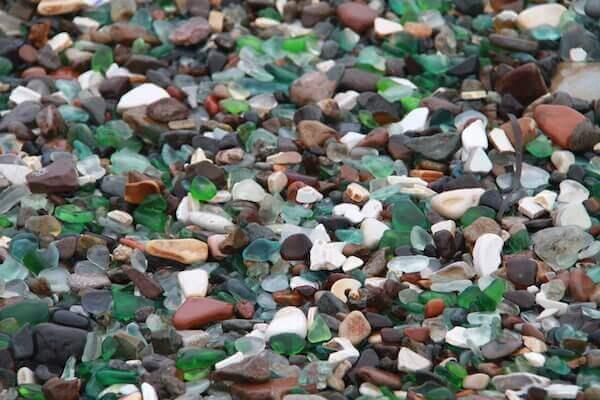 侵食されたガラスが落ちているビーチの写真