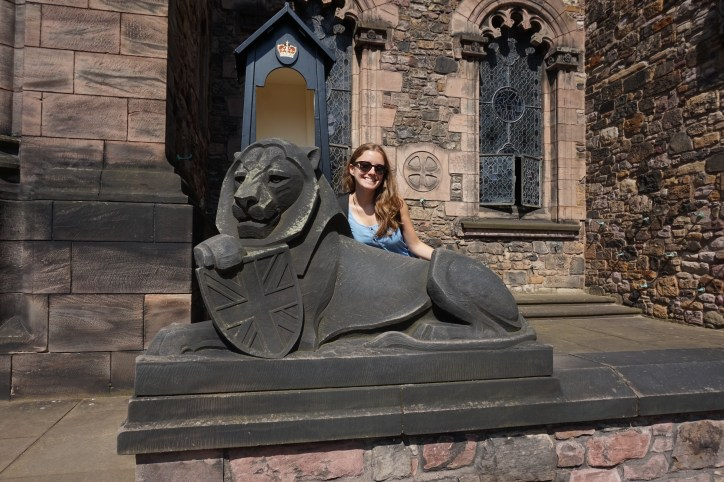 A girl posing with a stone black lion that carries a Union Jack shield.