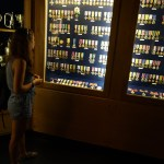 A girl looking at a wall of war medals encased in a glassed-cabinet.