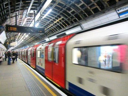 A train on the London Underground speeding past a stop.