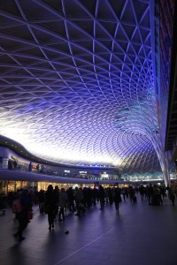 The blue designed ceiling at Kings Cross Station in London, England while passengers walk to their trains underneath it.