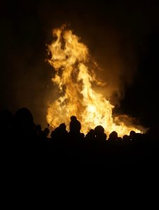 A big bonfire is seen beyond the dark silhouettes of people watching.