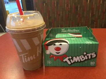 A box of TimBits and a large IceCap sit on a table at a Tim Hortons in Canada.