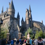 A replica castle of Hogwarts looms over a crowd of people.