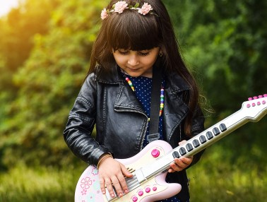 Little girl standing outside playing a small guitar - Adventures in NanaLand - Things to do with grandkids