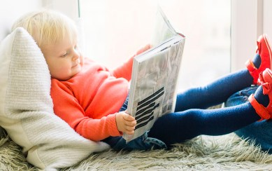 Toddler laying on a pillow reading a book - Adventures in NanaLand - Things to do with grandkids