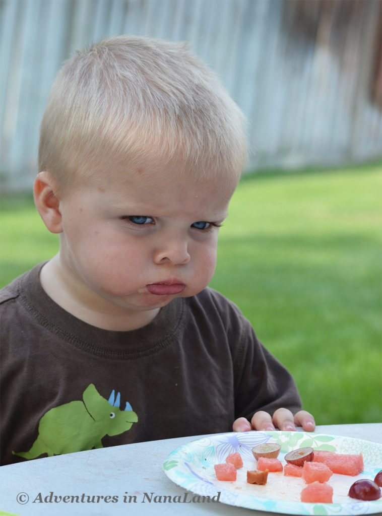 Child looking sad with a plate of fruit in front of him - Kid Friendly Meals - Adventures in NanaLand