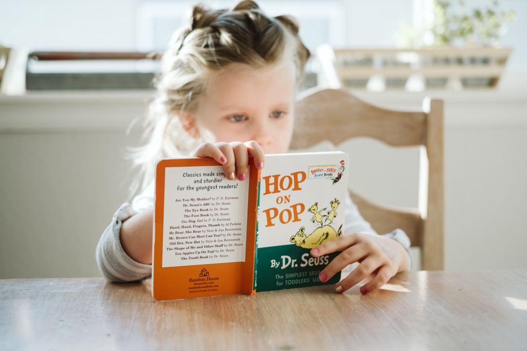 Little girl reading book called Hop on Pop - Adventures in NanaLand