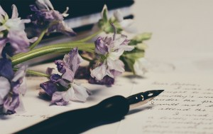 Fountain pen on lined paper with purple flowers lying nearby - Writing a life story - Adventures in NanaLand