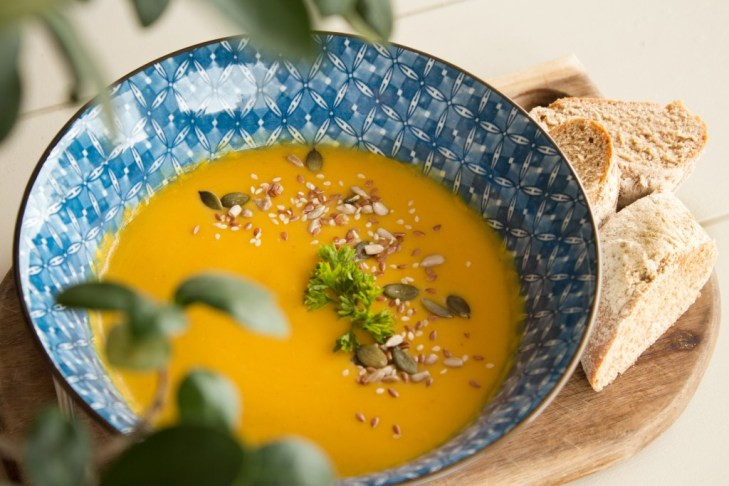 Pumpkin soup in a bowl with bread