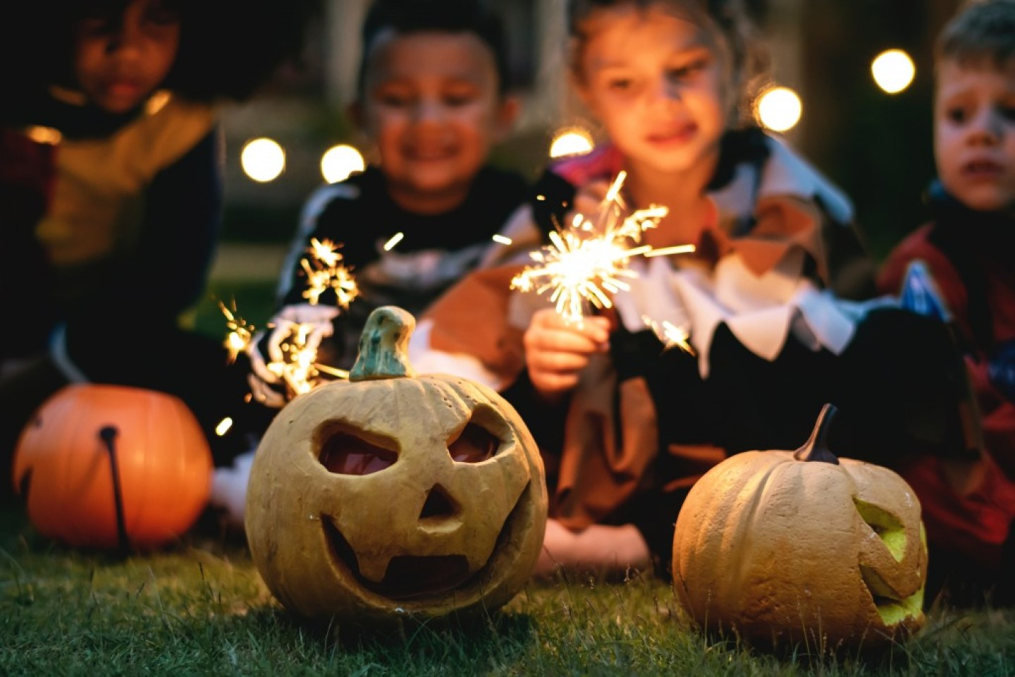 kids with sparklers looking at carved pumpkins