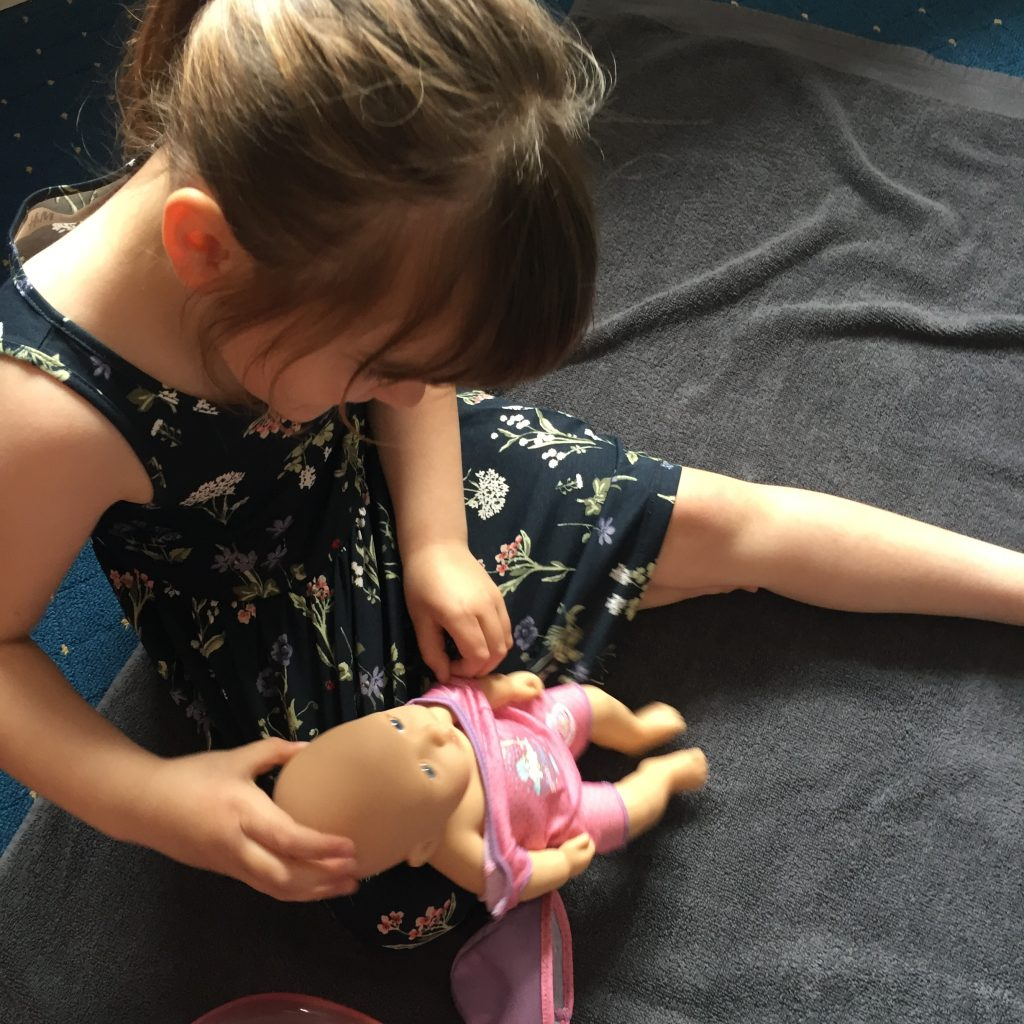 child playing with baby annabell doll