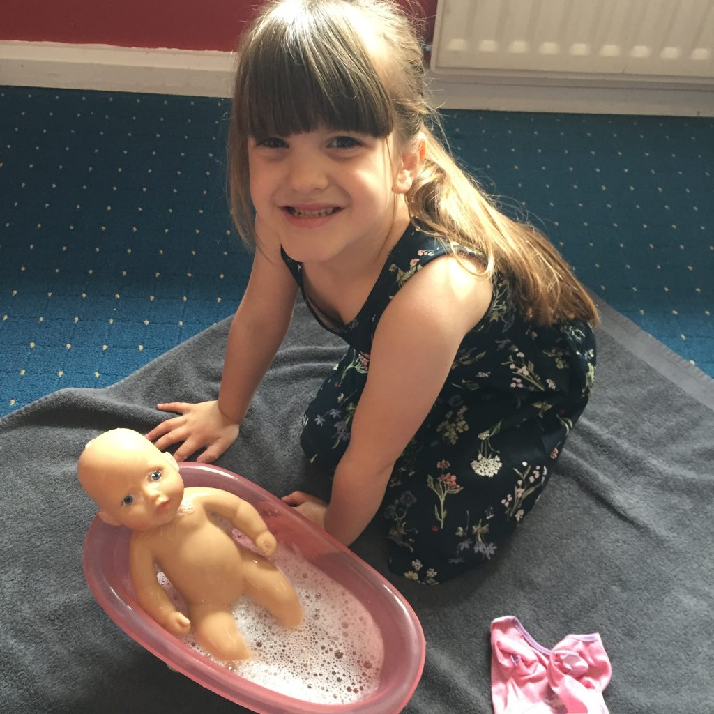 smiling child with baby annabell bathing doll
