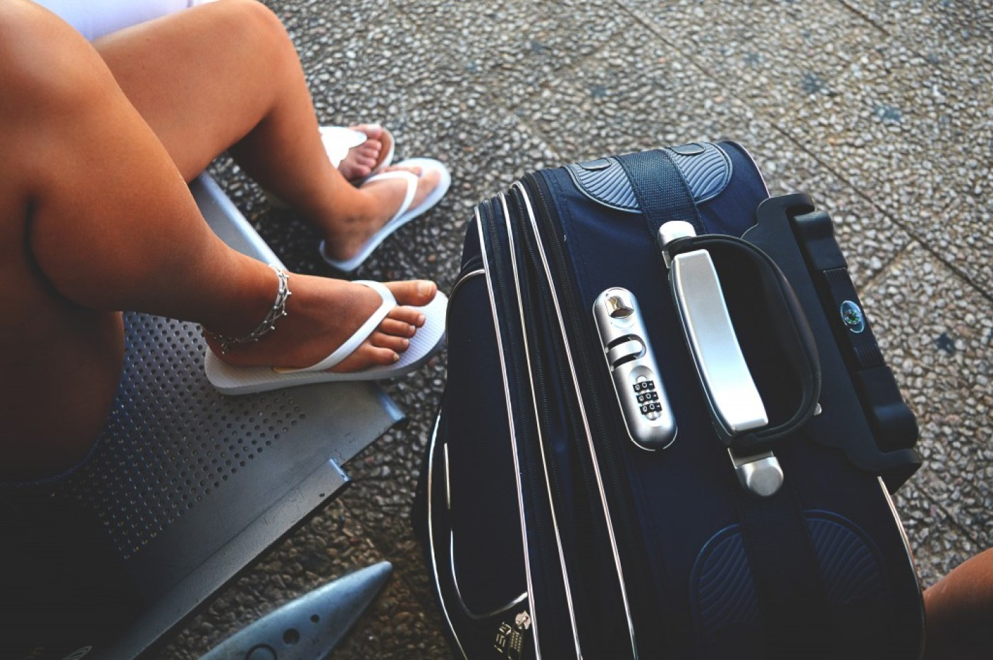 blue suitcase lady with flip flops
