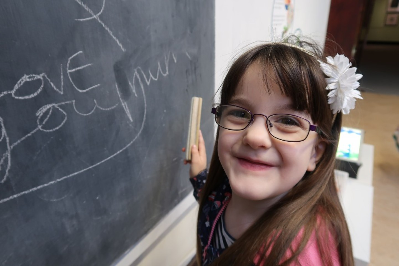 girl wearing glasses writing on blackboard