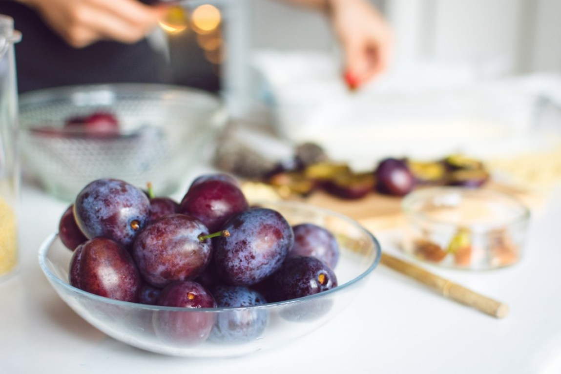 glass bowl with ripe plums
