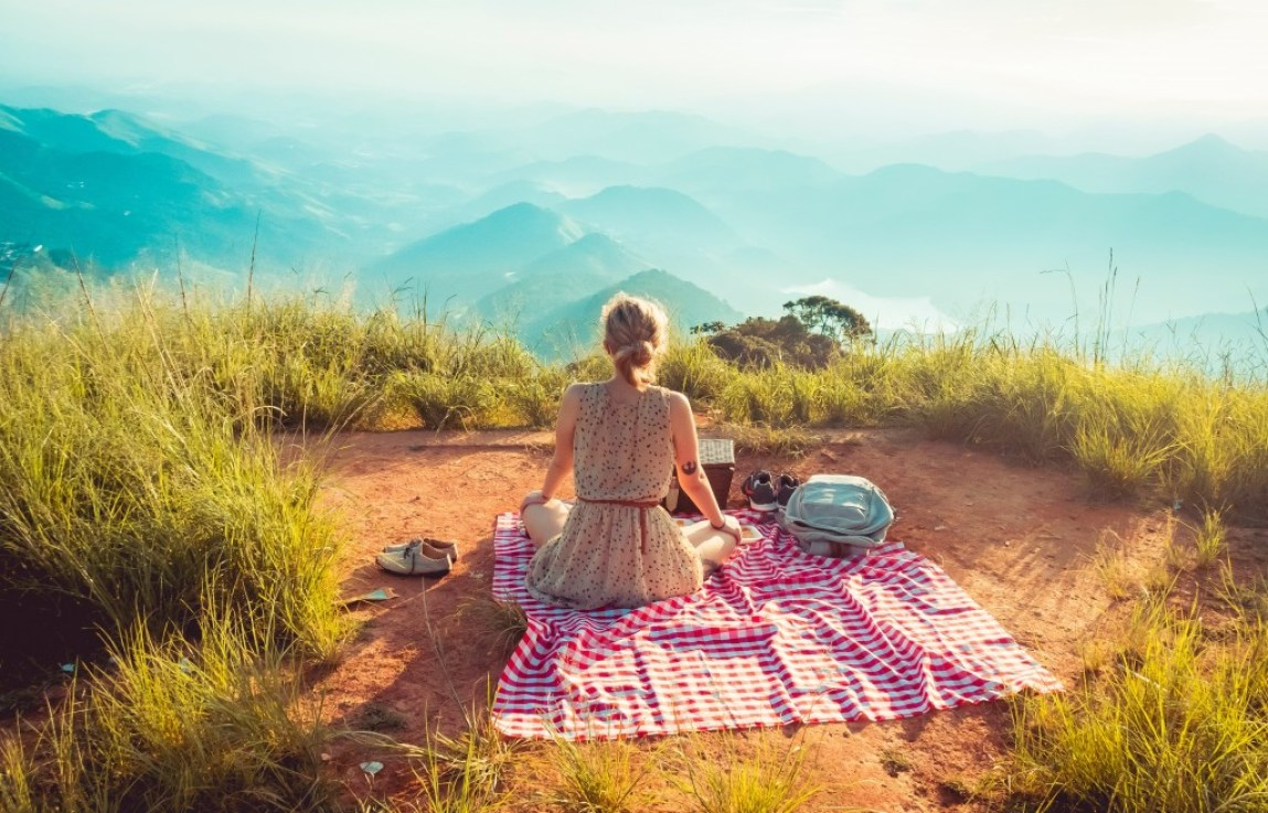 woman with picnic on a cliff top