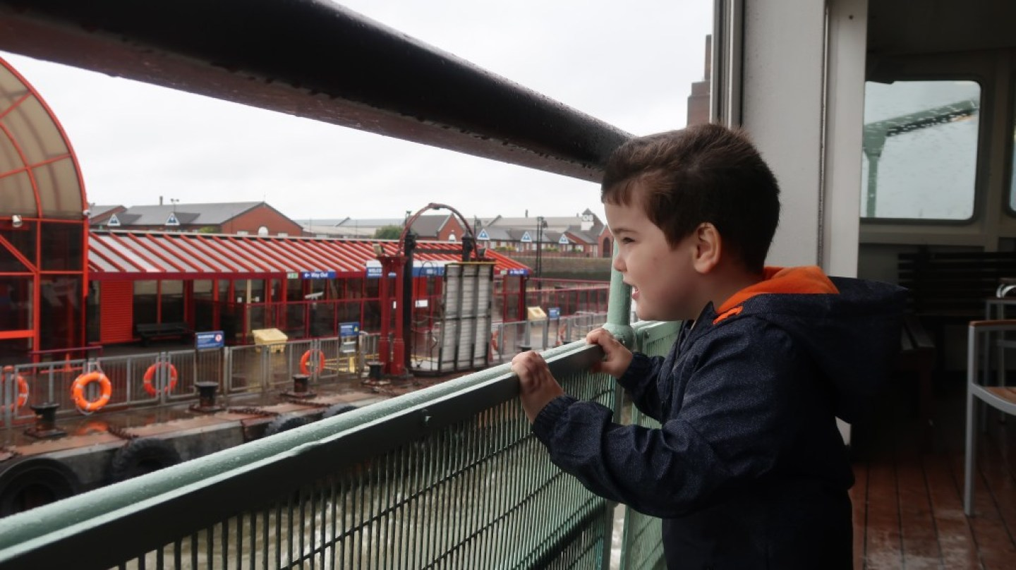 boy looking at pier head ferry terminal from the snowdrop