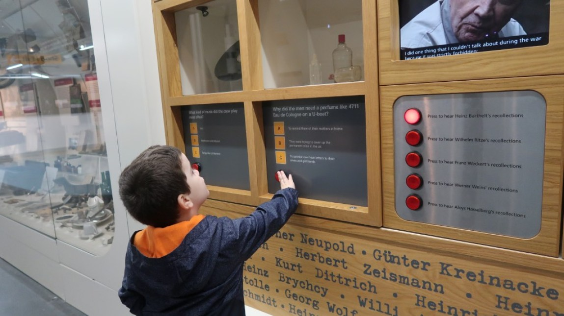 young boy exploring interactive displays at the uboat story liverpool