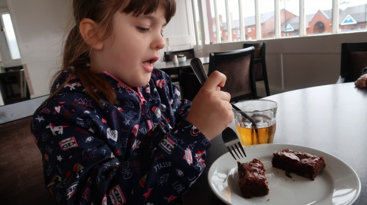 young girl enjoying chocolate brownie at ferry across the mersey