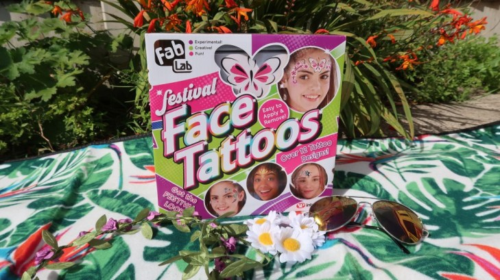 fablab face tattoos on picnic blanket in front of flower bed