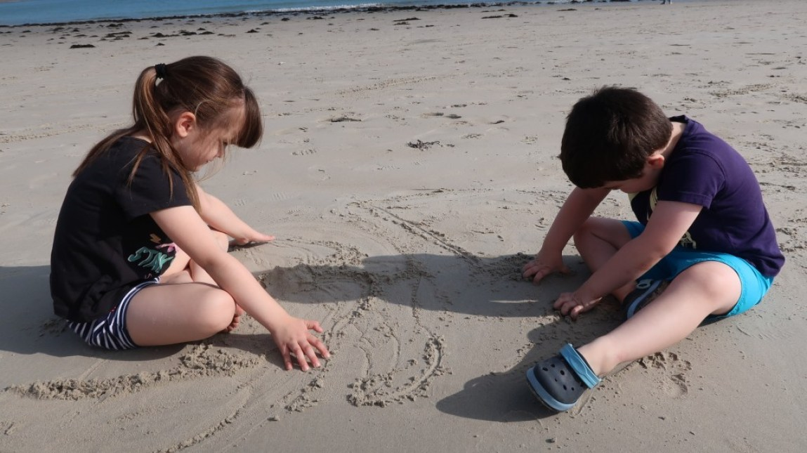 children drawing on sand on beach Ommaroo Hotel In Jersey