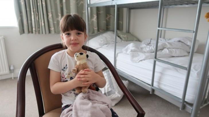 girl cuddling meerkat teddy in family room Ommaroo Hotel In Jersey