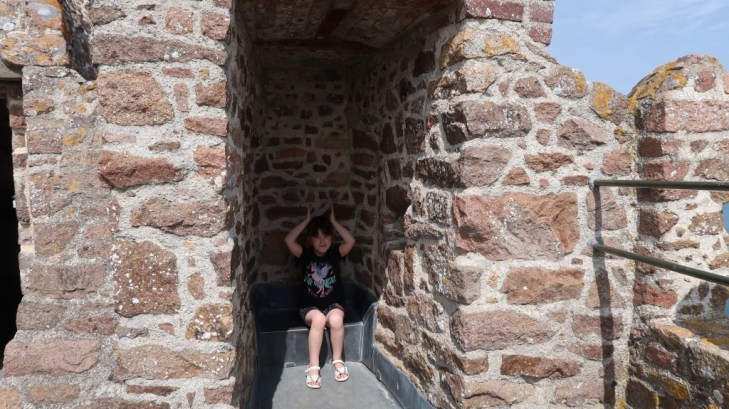girl sitting at Mont Orgueil Castle Jersey