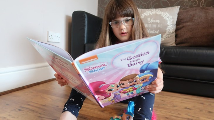 girl in glasses reading Penwizard Personalised Shimmer & Shine book