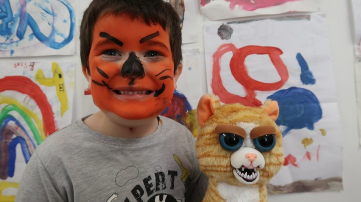 young boy with feisty pet face painted