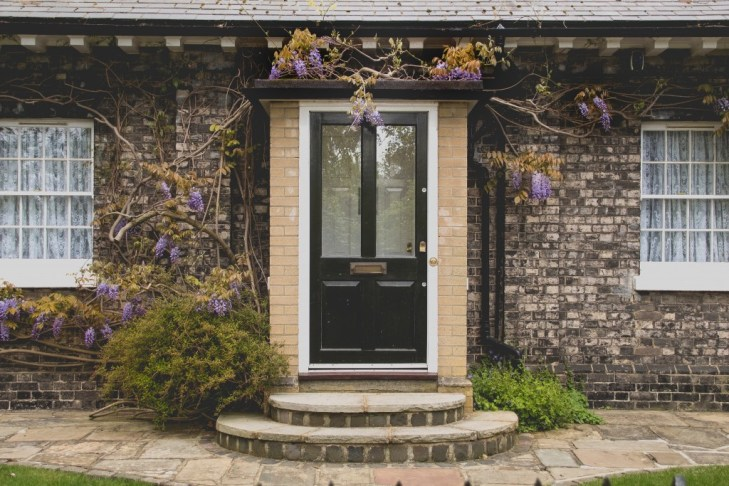 front door of cottage with climbing flowers