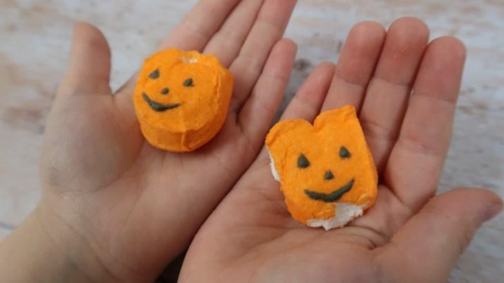 close up cjilds hands holding pumpkin shaped candy