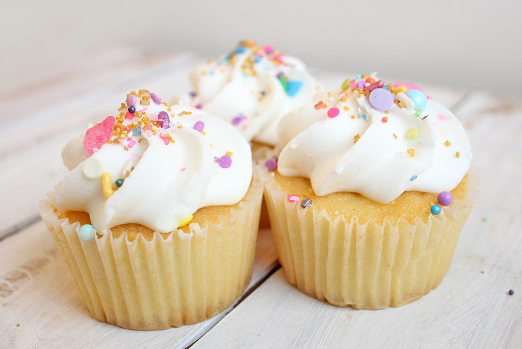 3 cupcakes with white frosting and colorful sprinkles