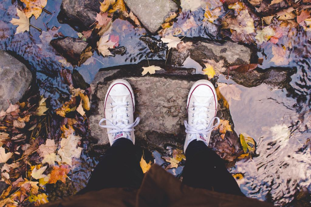 sneakers standing on rock with over water
