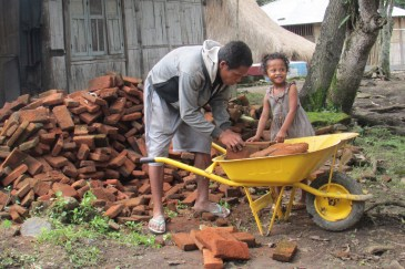 A little girl in Moni helps her father move bricks