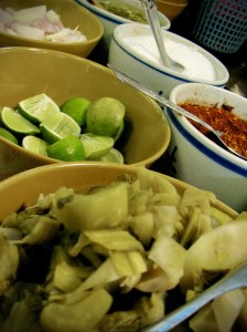 Onions, limes, pickled cabbage, chilli flakes, sugar, and chilli-vinager sauce are all on the table to add flavor to your Kho Soi