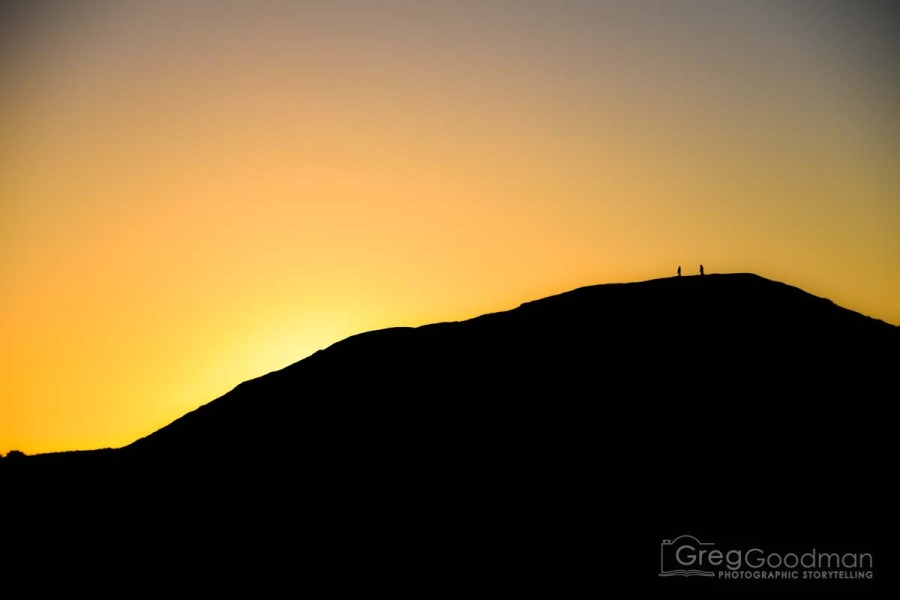 A couple watches the sunset from Goat Rock along the Sonoma Coast