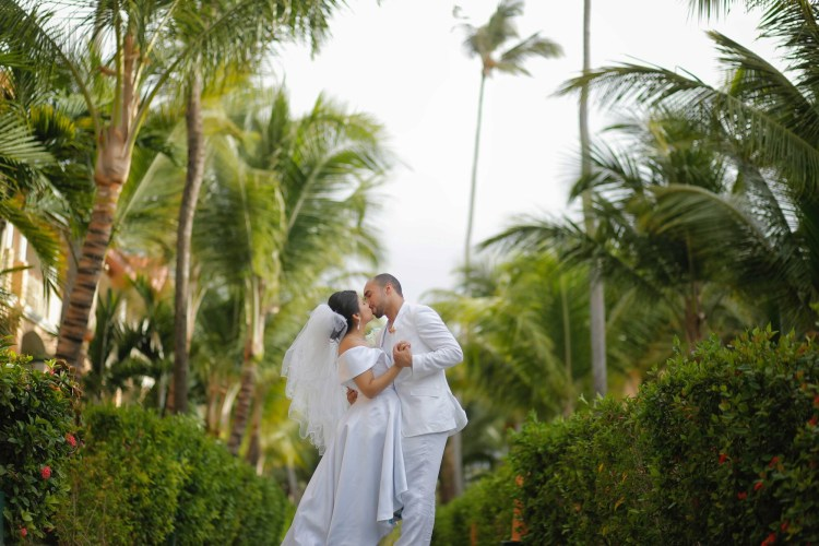 Destination wedding bride and groom kissing and dancing in an outdoor tropical setting