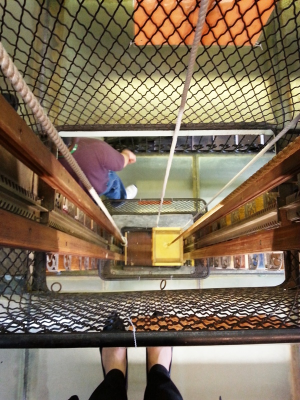 Looking down at the pulley system in the Troy Library used for moving books up and down in the stacks. By the way the floor here are milky glass blocks.